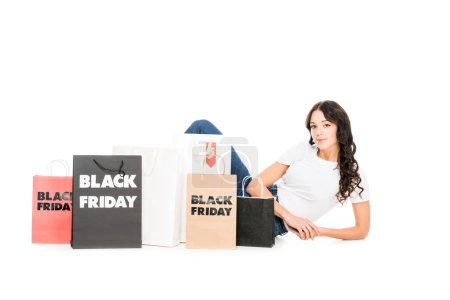 attractive shopaholic posing at shopping bags with black friday sale signs isolated on white