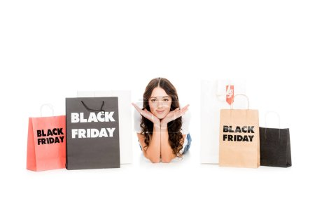happy stylish shopaholic lying at shopping bags with black friday symbols isolated on white