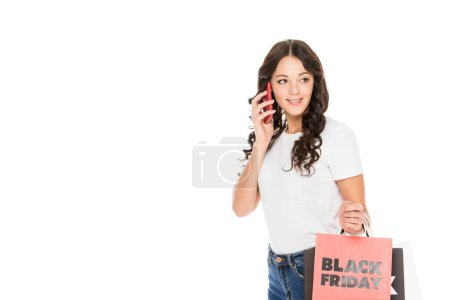 beautiful girl talking on smartphone and holding shopping bags with black friday sign isolated on white