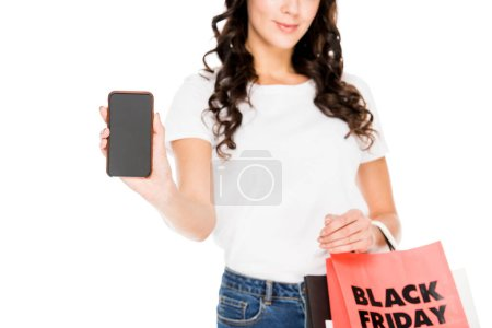cropped view of girl showing smartphone with blank screen and holding shopping bags with black friday sign isolated on white