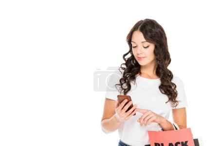 attractive shopper using smartphone and holding shopping bags with black friday sign isolated on white