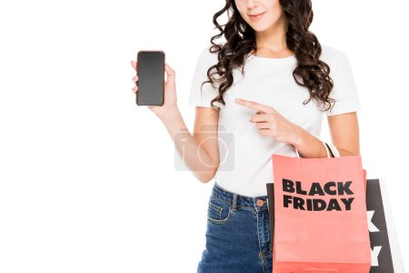 cropped view of girl pointing on smartphone with blank screen and holding shopping bags with black friday sign isolated on white