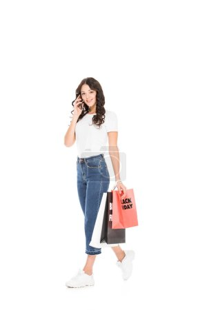 shopaholic talking on smartphone and holding shopping bags with black friday sign isolated on white