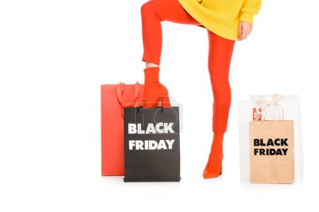 cropped view of female shopaholic posing near shopping bags on black friday sale, isolated on white
