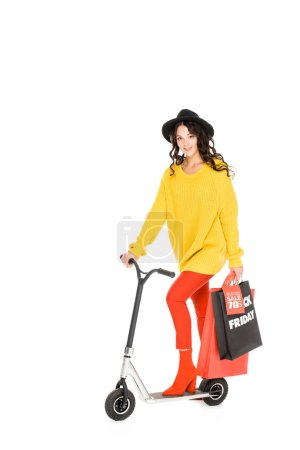 attractive girl riding scooter with shopping bags for black friday isolated on white