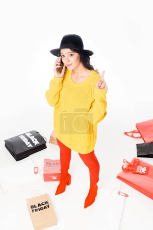 stylish shopaholic pointing up and talking on smartphone near shopping bags for black friday isolated on white