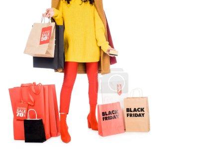 vista recortada de chica sosteniendo la tarjeta de crédito y bolsas de compras para el negro el viernes aislado en blanco