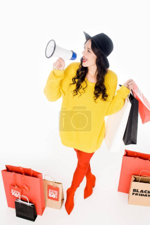 fashionable girl with shopping bags yelling into megaphone for promotion of black friday isolated on white