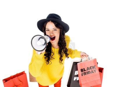 Photo pour Belle fille avec des sacs à provisions criant dans mégaphone pour la promotion du vendredi noir isolé sur blanc - image libre de droit
