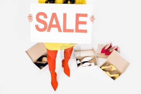 cropped view of girl holding sale sign isolated on white with shoes