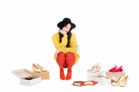attractive fashionable girl sitting near footwear boxes isolated on white
