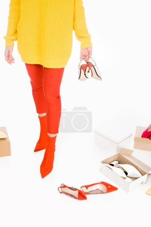 cropped view of stylish girl with footwear boxes isolated on white