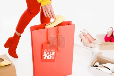 cropped view of woman with shopping bag and sale tag isolated on white with footwear boxes