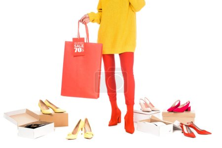 cropped view of shopaholic holding shopping bag with sale tag isolated on white with footwear boxes