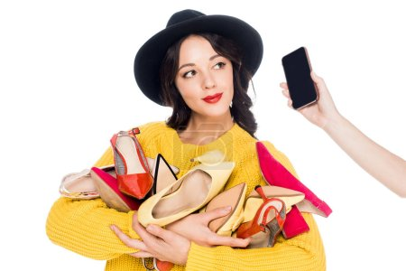 beautiful stylish woman holding heap of shoes while talking on smartphone isolated on white