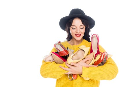 beautiful smiling girl holding heap of trendy shoes isolated on white