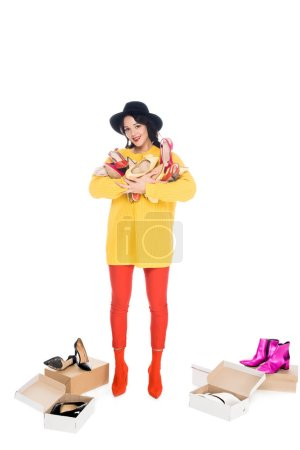 attractive stylish girl holding heap of high heels isolated on white
