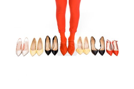 cropped shot of female legs and arranged footwear isolated on white