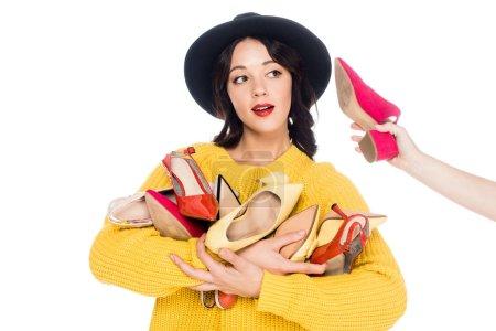 Photo pour Belle fille à la mode avec chaussure près de l'oreille tenant tas de talons hauts isolés sur blanc - image libre de droit