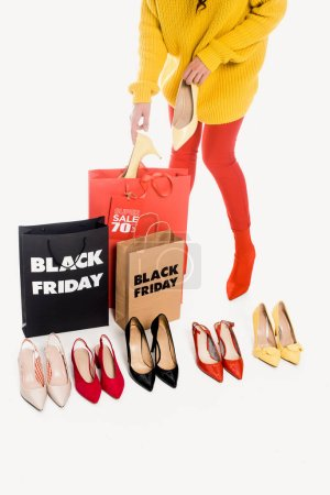 Photo for Partial view of woman, shopping bags with black friday inscription and stylish female footwear isolated on white - Royalty Free Image