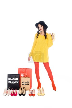 stylish woman standing near shopping bags with black friday lettering and arranged female shoes isolated on white