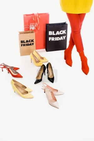 partial view of woman, shopping bags with black friday inscription and stylish female footwear isolated on white