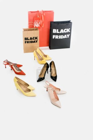 close up view of female footwear and shopping bags with black friday lettering on white background