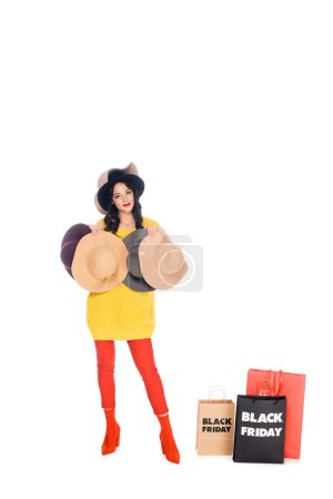 stylish woman with female hats standing near shopping bags with black friday lettering isolated on white