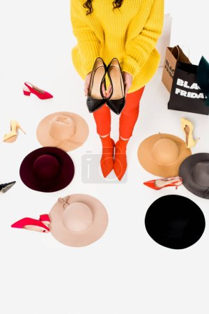 partial view of woman, female shoes, hats and shopping bags with black friday inscription isolated on white