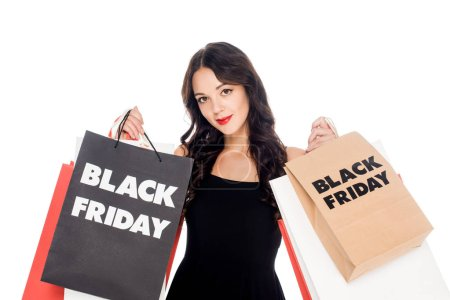 portrait of beautiful woman in black dress with shopping bags with black friday lettering isolated on white