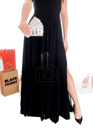 partial view of woman holding money with shopping bags and female footwear behind isolated on white, black friday sale concept