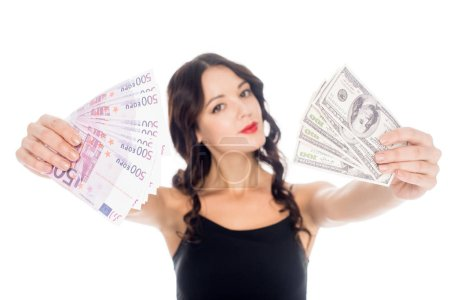 portrait of young woman showing dollar and euro banknotes in hands isolated on white