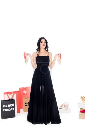 fashionable woman in black dress holding pair of shoes with female footwear and shopping bags behind isolated on white