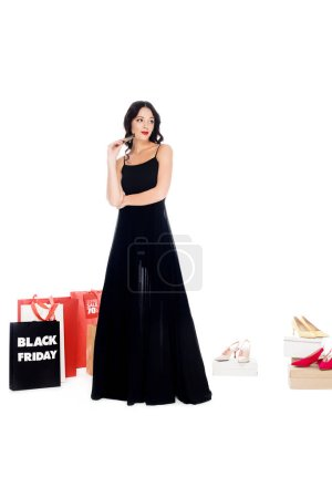 young woman holding credit card with shopping bags and female shoes behind isolated on white, black friday sale concept