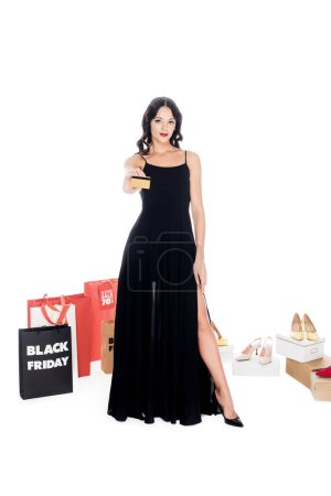 young woman holding credit card showing shopping bags and female shoes behind isolated on white, black friday sale concept