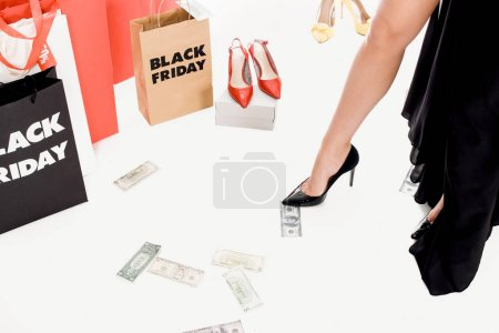 cropped shot fo woman, money, shopping bags with black friday lettering and footwear around isolated on white
