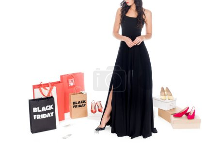 partial view of woman in black dress with shopping bags, money and shoes around isolated on white