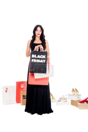 stylish woman in black dress holding shopping bags with black friday lettering isolated on white