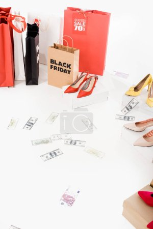 close up view of dollar banknotes, female footwear and shopping bags with black friday lettering on white background