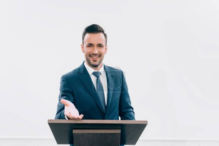 Photo for Smiling lecturer standing and gesturing at podium tribune during seminar in conference hall - Royalty Free Image