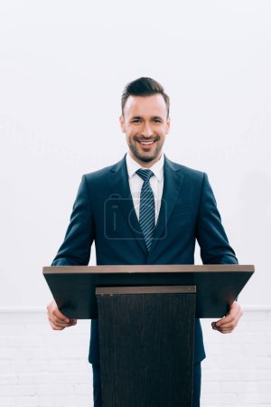 Photo for Smiling lecturer standing at podium tribune during seminar in conference hall - Royalty Free Image