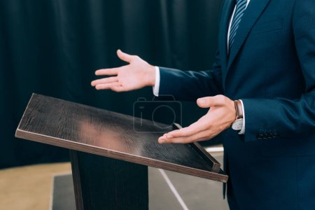 cropped image of lecturer standing and gesturing at podium tribune during seminar in conference hall