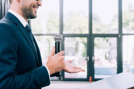 Photo for Cropped image of smiling speaker gesturing and talking into microphone at podium tribune during seminar in conference hall - Royalty Free Image