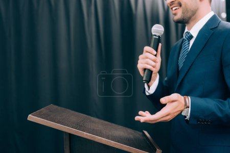 Photo for Cropped image of speaker gesturing and talking into microphone at podium tribune during seminar in conference hall - Royalty Free Image