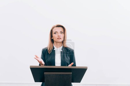 Photo for Attractive speaker gesturing and talking at podium tribune during seminar in conference hall - Royalty Free Image
