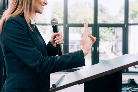 Photo for Cropped image of lecturer showing okay gesture at podium tribune during seminar in conference hall - Royalty Free Image