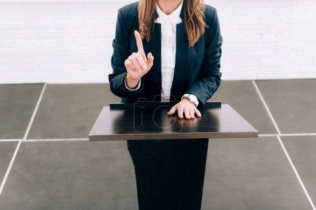 Photo pour Cropped image de présenter un doigt à la tribune du podium au cours du séminaire à la salle de conférence de maître de conférences - image libre de droit