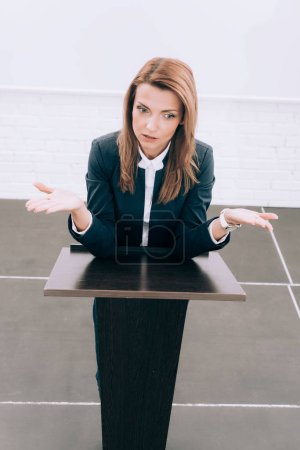 Photo for High angle view of attractive lecturer standing at podium tribune and showing shrug gesture in conference hall - Royalty Free Image