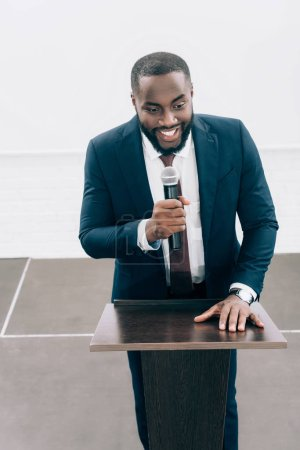 high angle view of smiling african american speaker talking into microphone during seminar in conference hall