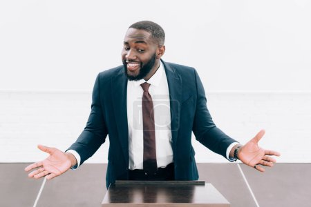 Photo for High angle view of smiling african american lecturer showing shrug gesture at podium tribune in conference hall - Royalty Free Image